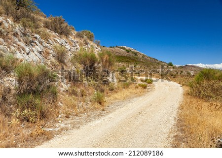 Dusty rural road at Pantokrator mountain foothill, Corfu, Greece - stock photo