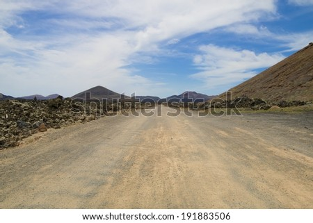 Dusty volcanic desert road leading into the distance on Lanzarote island, Spain - stock photo