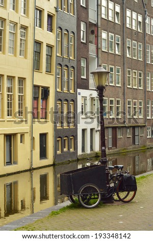 Dutch cargo tricycle locked on a lamppost in front of old houses by a canal in historic quarter of Amsterdam, Netherlands - stock photo