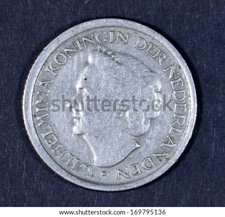 Dutch coin worth 25 cents with a picture of former Queen Wilhelmina. Isolated on black - stock photo