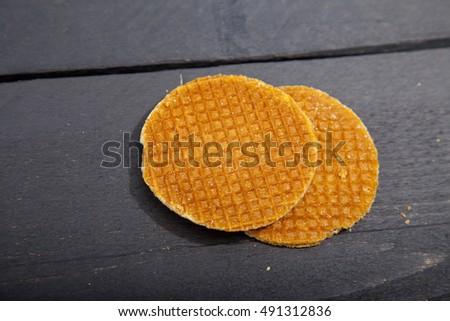 Dutch cookie stroopwafels on black wooden background