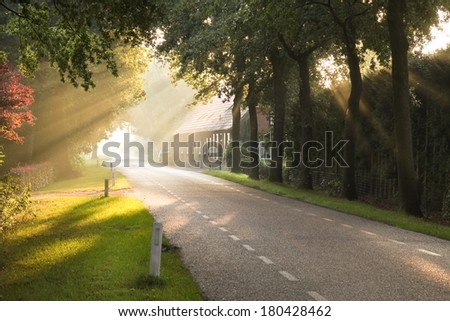 Dutch country road and farm in early morning sun after the rain - stock photo