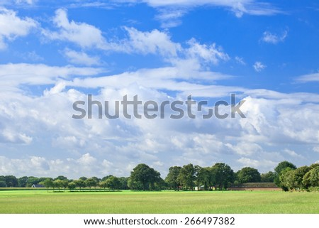 Dutch countryside with green trees and a blue sky with dramatic shaped white clouds. - stock photo