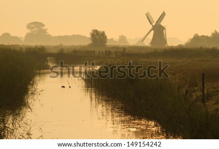 Dutch countryside with windmill during a summer sunrise.