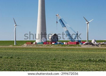 Dutch farmland with replacement of old wind tubines through enormous new wind turbines - stock photo