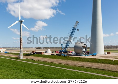 Dutch farmland with replacement of old wind turbines through enormous new wind turbines - stock photo