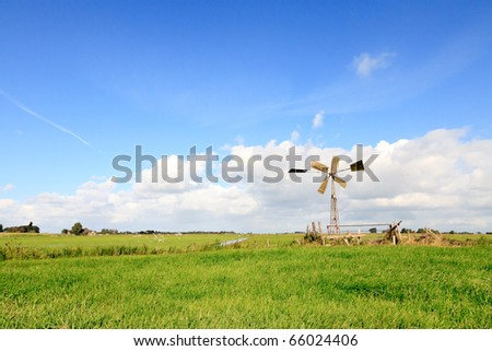 Dutch farmland with windmill under blue cloudy sky - stock photo