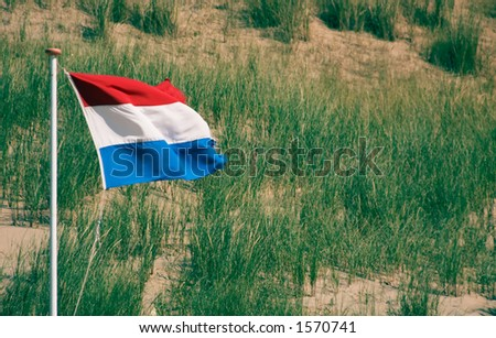 Dutch Flag against sand dunes - stock photo