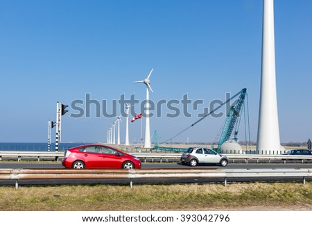 Dutch highway with cars along construction site new wind turbines - stock photo