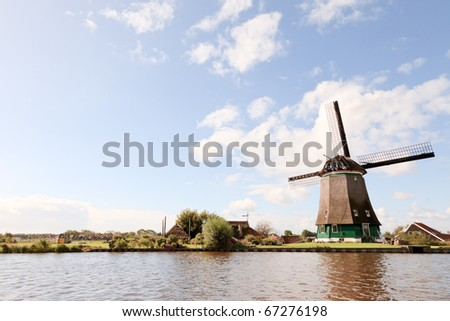 Dutch landscape with canal and windmill under blue cloudy sky - stock photo