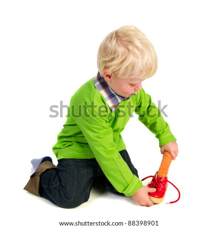 Dutch little boy is putting a carrot in his shoe for the horse of Sinterklaas - stock photo