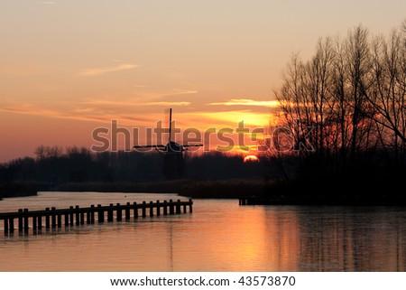 Dutch mill in winter evening light. Taken at the Rottemeren near Rotterdam, Netherlands - stock photo