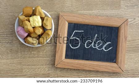 Dutch Pepernoten and the text 5 dec written on a chalkboard, typical Dutch treat for Sinterklaas on 5 december - stock photo