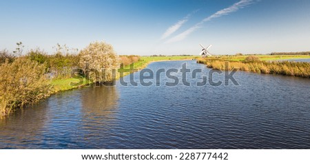Dutch polder landscape with a river with a rippling water surface and in the background a rotating historic windmill. - stock photo