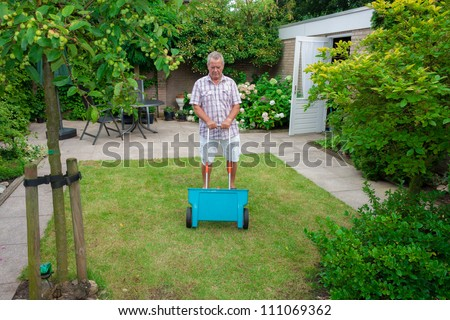 Dutch retired senior fertilising his grass lawn as retirement activity with a blue fertilizer dispenser on wheels