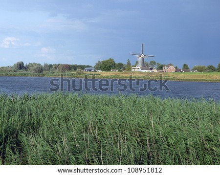 Dutch river landscape with windmill under cloudy blue sky on a sunny summer's day - stock photo