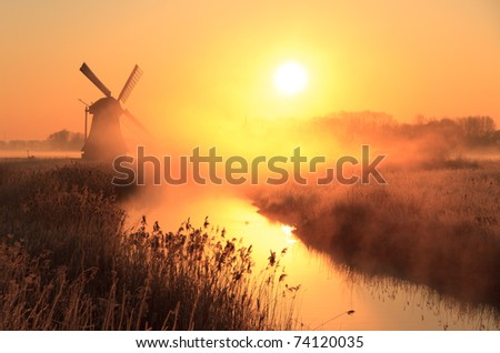 Dutch sunrise with traditional windmill and a canal in the spring fog. - stock photo