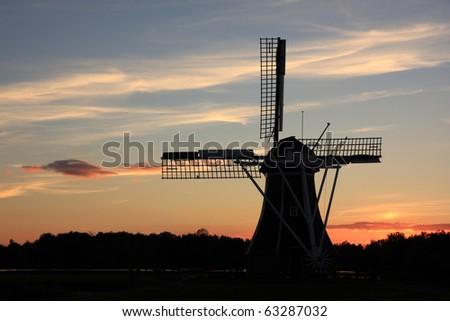 Dutch windmill at autumn sunset. - stock photo