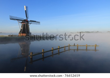 Dutch windmill in the fog at a lake in Holland. - stock photo