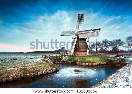 Dutch windmill in winter after sunset - stock photo