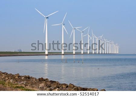 Dutch windmills along the coastline, mirroring in the calm sea - stock photo