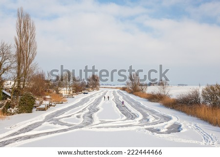 Dutch winter landscape with skaters on a canal - stock photo