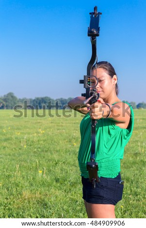 Dutch woman aiming with bow and arrow in nature