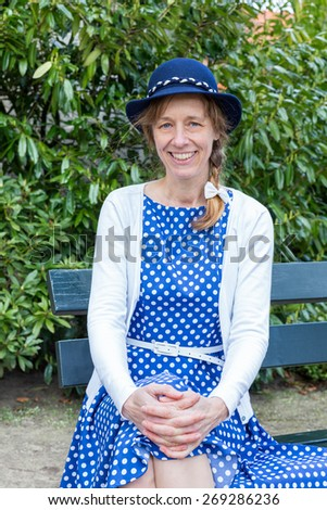 Dutch woman in old-fashioned clothes of the forties sitting on bench in park. The caucasian woman is posing looking at the camera - stock photo