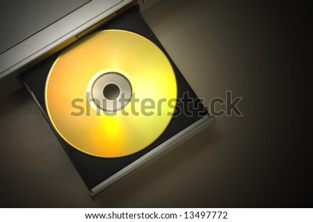 dvd player with open tray with a gold disk with dramatic light - stock photo