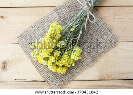 Dwarf everlast flowers bouquet and napkin on light wooden table, selective focus - stock photo