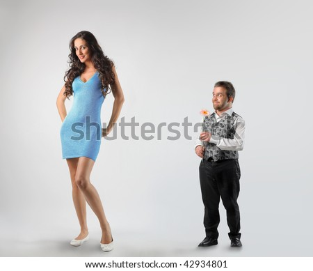 dwarf paying court to tall woman - stock photo