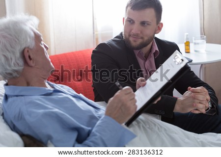 Dying man signing his testament in the presence of notary - stock photo