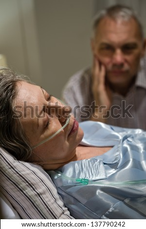 Dying old woman in hospital bed with caring man - stock photo