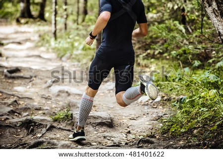 dynamic athlete running marathon in woods. legs in compression socks