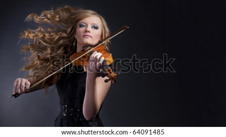 Dynamic, beautiful woman playing violin - stock photo