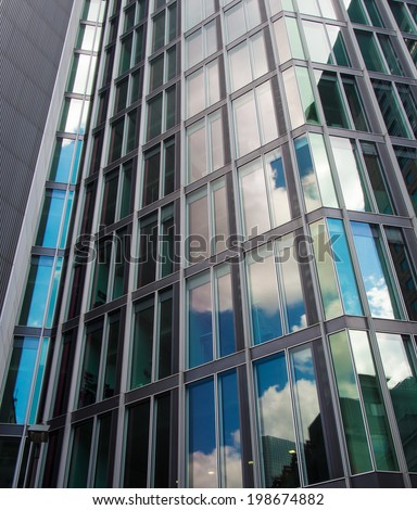 Dynamic glass facade with reflection of the sky, Frankfurt Fascinating modern architecture in one of the most dynamic business environments in Europe - stock photo