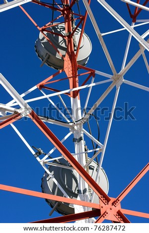 Dynamic perspective of a red and white communication tower with antennas against deep blue sky - stock photo