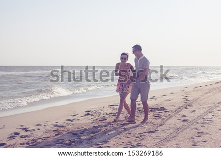 Dynamic shot of happy smiling couple. Focus on guy. Walking on the beach. Holding each other and laughing - stock photo
