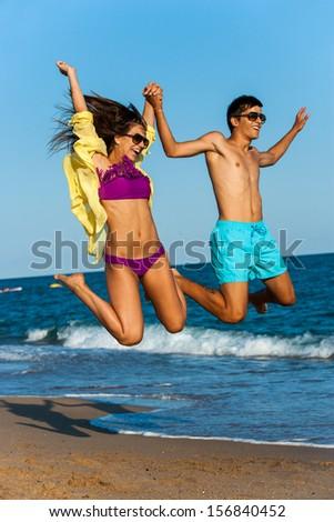 Dynamic teen couple in swim wear jumping on beach. - stock photo
