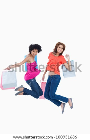 Dynamic teenagers energetically leaping after going shopping - stock photo