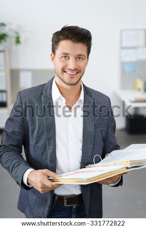 dynamic young business man standing at the office holding a folder - stock photo