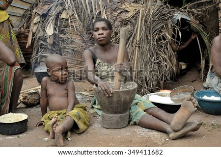 DZANGA-SANHA FOREST RESERVE, CENTRAL-AFRICAN REPUBLIC (CAR), AFRICA, 2008 NOVEMBER 2:Jungle of CAR. Africa. Jungle of the Central-African Republic. Baka woman cooks food, crushing a flour in a mortar  - stock photo