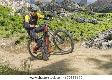 E bike rider in middle age enjoys the power of the e bike on a steep uphill trail.