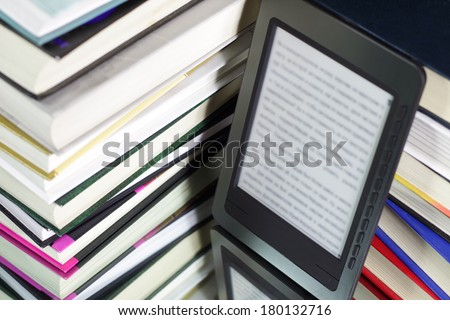 E-book reader against the background of a stack books - stock photo