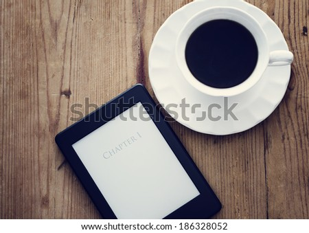 E-book reader and coffee cup on wooden table - stock photo