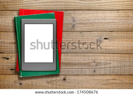 E-book reader and old books on wooden background - stock photo