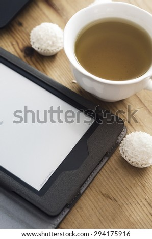 E-book reader and tea cup on wooden table - stock photo