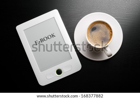 E-book reader and white coffee cup on table - stock photo