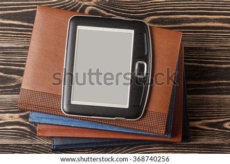 E-book reader close-up on wooden background - stock photo