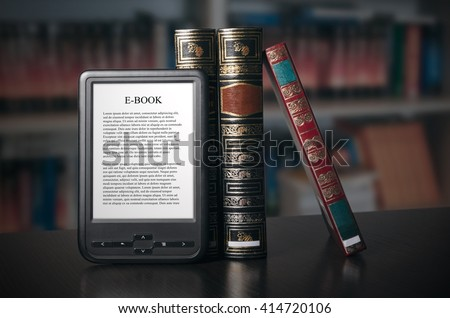 E-book reader device on desk in library. Alternative for traditional books - stock photo